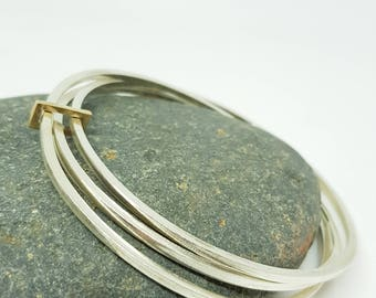 Clara by Fedha - stylish set of three polished sterling silver bangles with solid gold link, uncluttered, understated