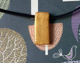 A gold painted rectangular pendant necklace
