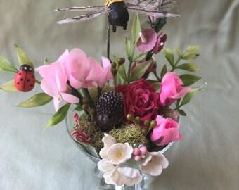 Handmade Spring summer Garden collage with hedgehog bee ladybug vintage flowers in an antique glasss
