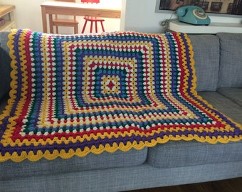 Brightly coloured large granny square crocheted blanket
