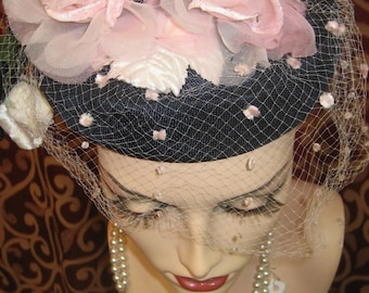 """1950's, 22"""" round, hat of midnight blue silk, with pink silk roses atop of crown."""