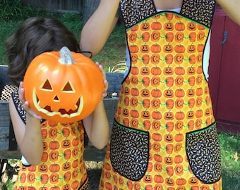 Mommy and me Halloween apron set done in a quality cotton of bright orange, yellow and black jack-o-lanterns,  great for carving pumpkins.