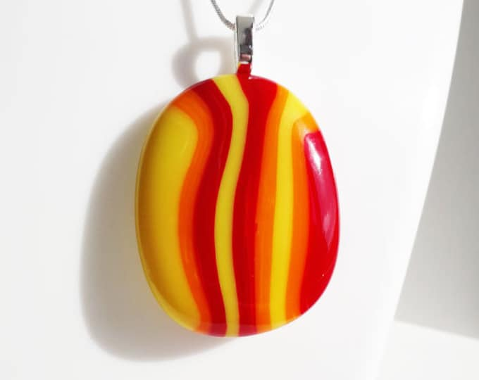 Fused glass pendant, in red orange and yellow stripes.