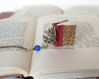 Collana con libro rosso bordeaux con foglie disegnate,  pendente con foglia di quercia e perla blu