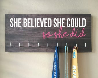 """Race Medal Holder - """"She believed she could SO SHE DID"""" white and pink with gray woodgrain background"""
