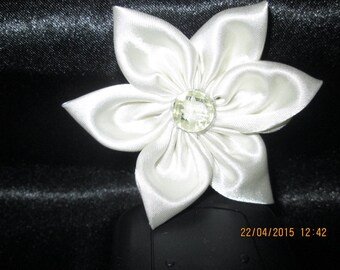 Ivory satin with a flower is adorned with a transparent white button with in the Middle a white flower