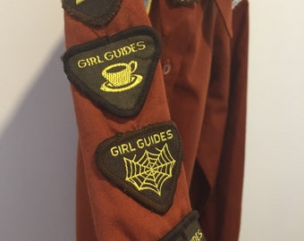 Vintage Girl Guide Brownie uniform with badges and leather purse belt
