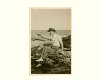 Vintage photo of a young and smiling man on the beach, wearing a boater