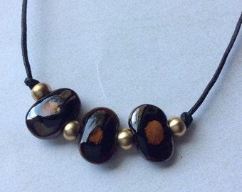 Kazuri unisex choker necklace.Mustard yellow and antique gold flat ceramic beads. Raw brass. Waxed cotton cord.