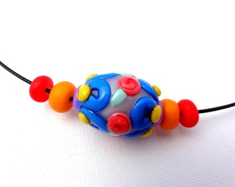 Multi-colored glass like bead made from clay by Marie Segal