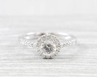 White sapphire and diamond halo engagement ring in 18 carat white gold