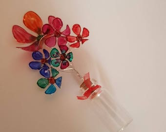 Resin flowers in tiny glass bottle. Each flower is individually hand-painted.