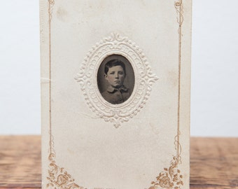 Antique Tintype of young boy in embossed paper frame.