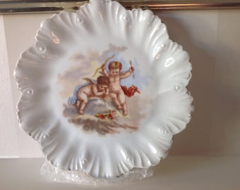 Vintage porcelain decorative plate with cherub with bow and arrow design, scolloped edge, lovely for a display cabinet