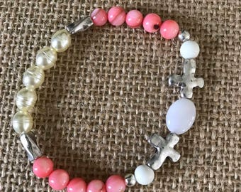 Coral and white beaded bracelet with silver cross and accents.