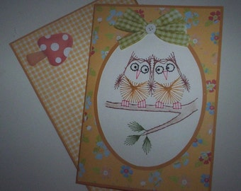 Stitched note card with matching envelope of two owls sitting on branch.
