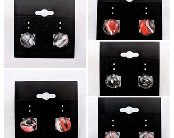 Red, black, and white stud earrings, fluid art
