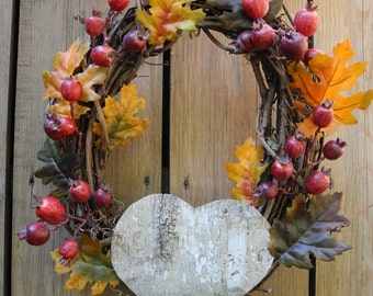 Beautiful fall wreath with leaves, rose hips, and a natural birch bark heart.