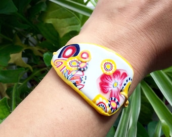 Bracelet made of polymer clay, yellow and pink floral motifs on white background