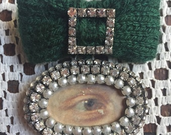 Lover's Eye brooch with green knitted bow