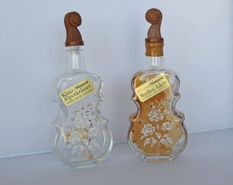 Two Small Vintage Violin Shaped Liquor Bottles with White Flowers, and Gold Highlights.