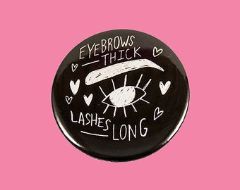 eye brows thick, lashes long | 2.25 inch pin back button
