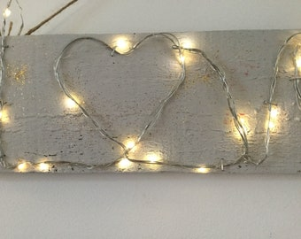 Love, wire word art with L ED lights on rustic wood.