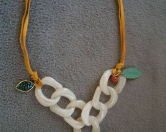 tan leather and acrylic chain necklace with a brass and bone pendant