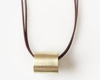 Sturdy brown leather necklace with a large, round brass pendant