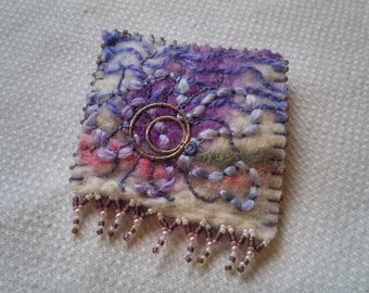 A hand crafted upcycled mixed media hand embroidered and beaded felt brooch in shades of purple with repurposed broken jewellery