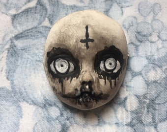 Possessed babyface brooch