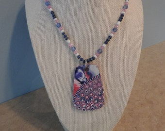 Pink and blue polymer clay pendant with swirls and dots on the bottom on a beaded necklace