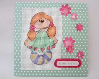 Cross stitch card with a little girl on a spotty background with pink flowers  and the wording 'little rascal'