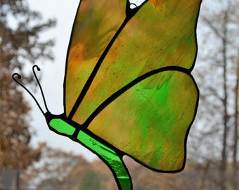 Stained glass butterfly suncatcher with streaky orange and green wings and bright green body, 5 x 7