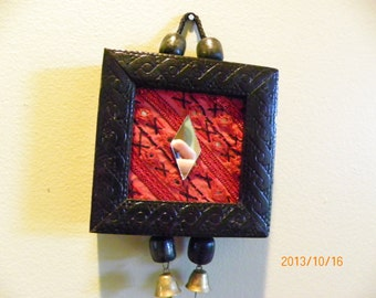 small Indian red framed wall hanging with bells.