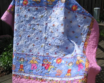 """Little Girls Having Fun Roller Skating quilt 55X60"""" in bright Pink and Purple prints with daisys and butterflies throughout the prints."""
