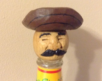 Hand carved hot sauce bottle top