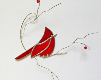Bright and colourful red stained glass cardinal suncatcher on 3- dimentional wire branch with berries