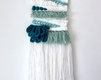 Turquoise and white woven wall hanging