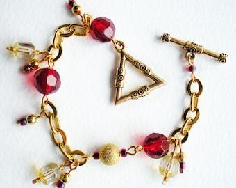 Bracelet à breloques fait main avec des perles de verre rouge et chaîne en or