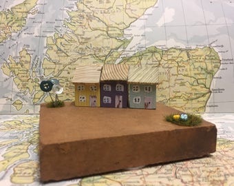 A row of 3 wooden houses sat on a vintage tile