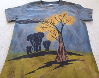 A family of elephants walking underneath a tree, mountains in the distance, a baby on the back, woman's large discharge and dyed t-shirt