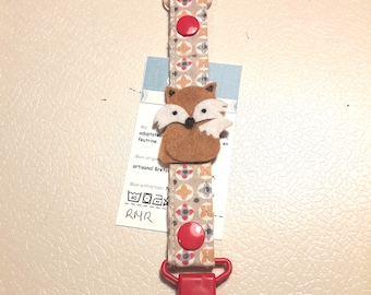 Pacifier clip in beige and orange fabric with a brown felt Fox