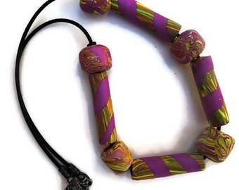 Handmade violet and green polymer bead necklace with alternating tube and round beads on a 20 inch buna cord closed by  a toggle clasp