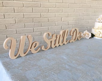 Wooden sign 'We Still Do' in script letters. Freestanding wood sign for a Wedding, Anniversary, or Vow renewal. Gift idea for couples