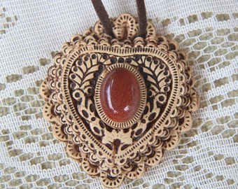 Birch bark pendant with semi-precious stone from Ural Mountains on leather cord .