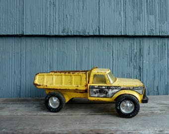 Nylint Dumper Truck, Rusty yellow pick-up toy truck, construction equipment toy, hauler