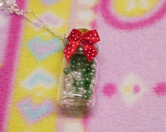 Green gem and red ribbon bottle necklace