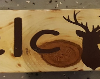 Welcome sign with deer Head. Solid wood piece with knots, dark brown lettering.