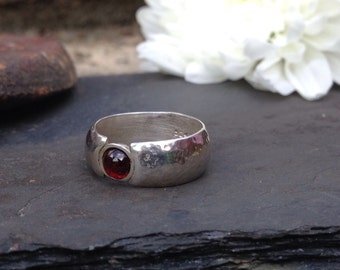 Handmade hammered silver ring with a garnet stone.